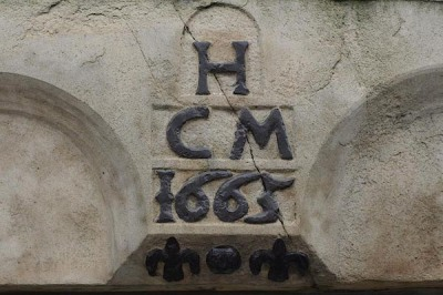A 17th century triad incorporated into a commemorative plague carved into a stone door lintel in a building in Market Street, Lower Holker, Cumbria, England.
